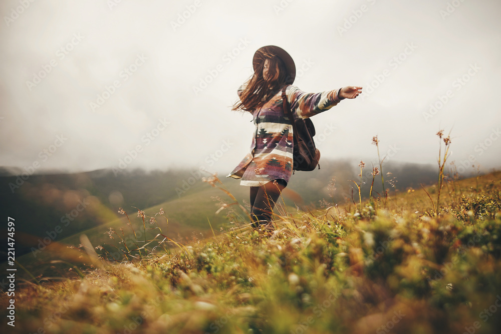 Fototapety, obrazy: happy traveler hipster girl in hat, walking with backpack and smiling in windy mountains in clouds. space for text. amazing atmospheric emotional moment. travel and wanderlust concept