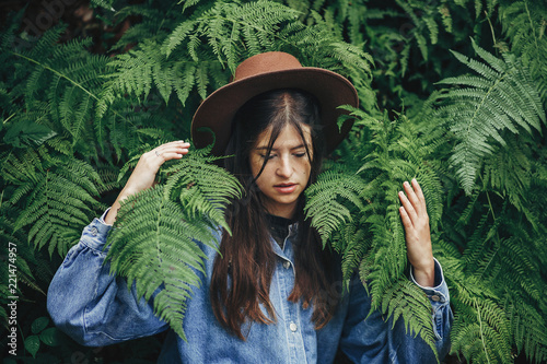 Fototapeta stylish hipster girl in hat sitting in fern bushes, among fern leaves in forest. creative portrait of woman traveler. environmental concept. space for text. atmospheric moment obraz