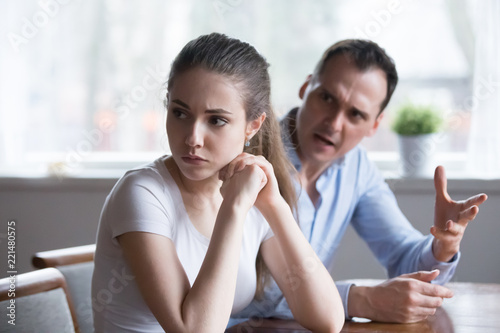 Offended woman sitting back to lover looking away avoiding