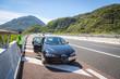 Panne auf der Autobahn: Junger Mann in Warnweste wartet am Pannenstreifen auf den Pannendienst