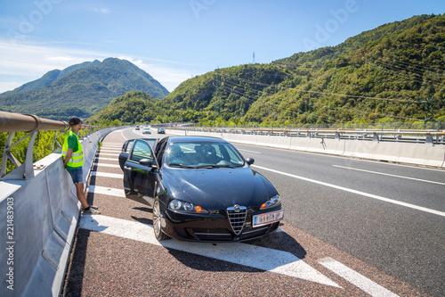 Fotografie, Obraz  Panne auf der Autobahn: Junger Mann in Warnweste wartet am Pannenstreifen auf de
