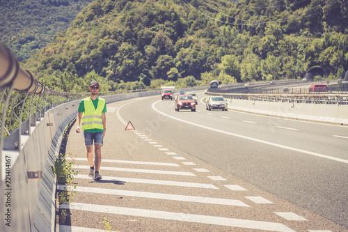 Fotografie, Obraz  Panne auf der Autobahn: Junger Mann in gelber Warneweste stellt Pannendreieck zu