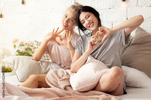 Fotografija  Portrait of young lovely multinational women sitting in light interior in loft style and looking homey