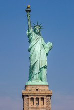 A View Of The Statue Of Liberty In New York, With A Clear Blue Sky Behind