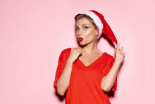 Young Woman Wearing Santa Claus Cap With Red Lips On Pink Background.  Celebration Holiday Concept.
