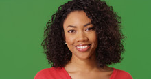 Portrait Of Pretty Black Millennial Female Smiling At Camera On Green Screen