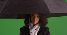 Pretty African American Woman Holding Umbrella Looking At Camera On Green Screen