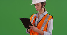 Woman Worker In Orange Vest With Tablet Computer And Hard Hat On Greenscreen