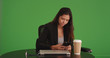Young business female texting sitting at cafe table on green screen