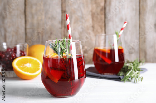 Fototapeta Tasty refreshing cranberry cocktail with rosemary on table