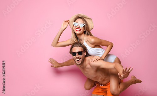 Obraz na plátně Happy young couple in beachwear on color background