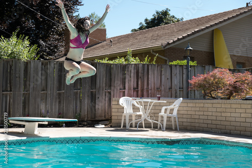 Young brunette woman jumps off diving board arms up in the ...