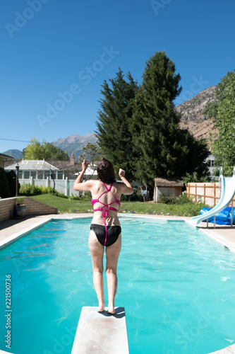 Young woman on the edge of a diving board preparing to jump ...