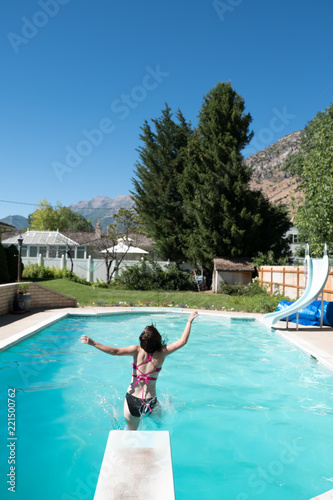 Young woman jumps off diving board into a backyard swimming pool ...