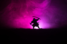 Fighter With A Sword Silhouette A Sky Ninja. Samurai On Top Of Mountain With Dark Toned Foggy Background.