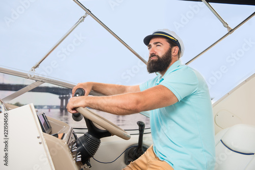 Spoed Foto op Canvas Zeilen A young guy with a beard swims on the yacht at the helm