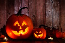Two Fun Halloween Jack O Lanterns. Night Scene With A Rustic Wood Background.