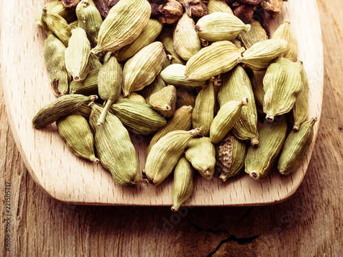 Deurstickers Kruiderij Green cardamom pods heap on wooden spoon