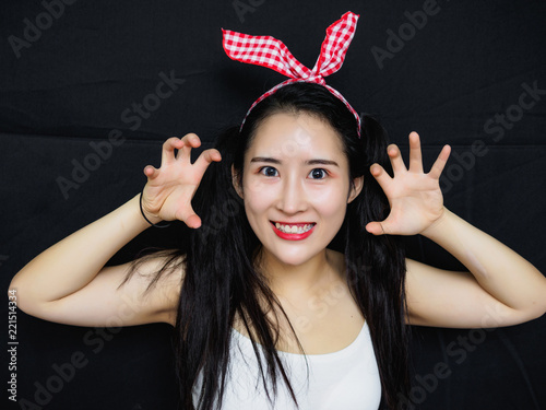 Fotografía  Portrait of sexy Chinese woman with long black hair, pink hair ribbon and white halter against black background, smiling at camera and make threatening gestures