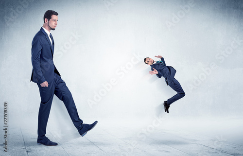 Fotografie, Obraz  Big businessman kicking small businessman who is flying away with his briefcase