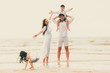 Happy family goes vacation on the beach in summer.