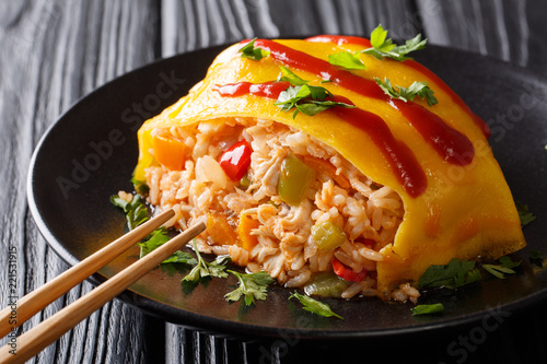 Japanese cuisine: omurice with rice, chicken and vegetables close-up on the table. horizontal