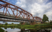 Railway Bridge Made Of Iron Structures, Against A Cloudy Sky Background