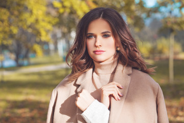 Autumn beauty. Perfect woman in beige coat outdoor. Girl walking in autumn park