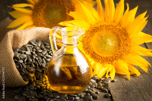 Fototapeta Closeup photo of sunflower oil with seeds on wooden background. Bio and organic product concept. obraz