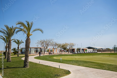 Fotografie, Tablou  Golf clubhouse with palm trees, buggies and putting green at golf course in Spai