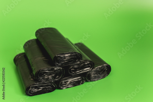 Fotografie, Obraz  New black rolls of garbage bags against a green background