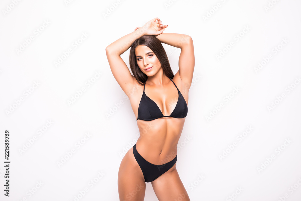 Fototapeta Slim body of young woman in black bikini isolated on white . Girl with healthy sporty figure isolated on white background - obraz na płótnie