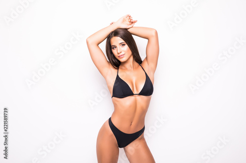 Obraz Slim body of young woman in black bikini isolated on white . Girl with healthy sporty figure isolated on white background - fototapety do salonu