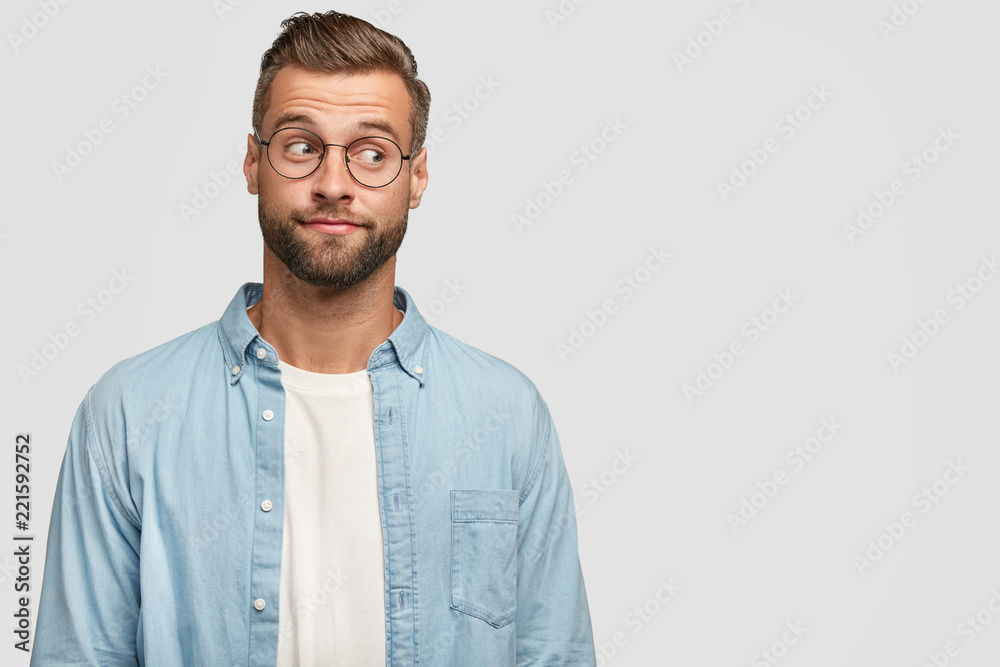 Fototapeta Isolated shot of funny bearded man designer or freelancer looks thoughtfully aside, thinks on how climb career ladder, wears casual shirt and round spectacles, isolated on white wall with copy space