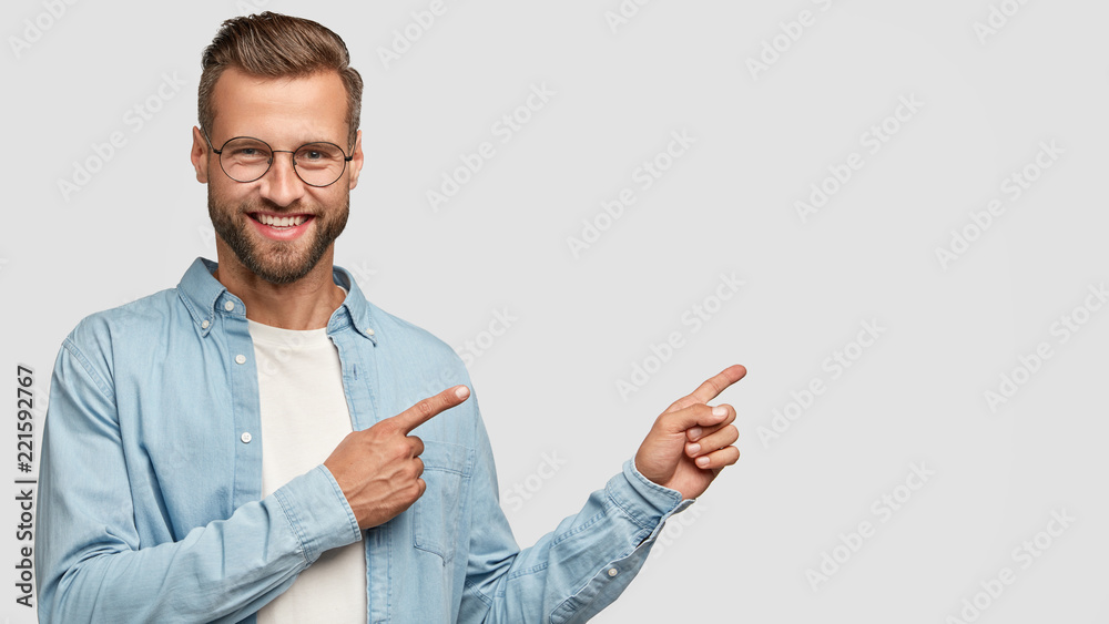 Fototapety, obrazy: Positive unshaven man looks and points at upper right corner with both index fingers, smiles with approval, suggest going there, sees something positive and very interesting, isolated on white wall