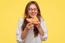 Photo Of Teenager Enjoys Delicious Slice Of Pizza, Likes This Taste, Closes Eyes From Pleasure, Has Good Appetite, Dressed In Casual White Shirt, Isolated Over Yellow Background. Hungry Woman Indoor