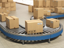Cardboard Boxes On Conveyor Roller In Distribution Warehouse, Delivery And Packaging Service Concept.