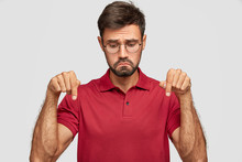 Photo Of Discontent Caucasian Man Purses Lips With Displeased Expression, Looks Down, Feels Offensed, Points With Both Index Fingers On Floor, Wears Round Glasses, Red Spectacles, Isolated On White