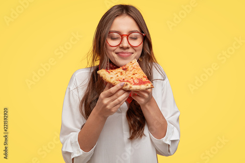 Fotografie, Obraz  Photo of teenager enjoys delicious slice of pizza, likes this taste, closes eyes from pleasure, has good appetite, dressed in casual white shirt, isolated over yellow background