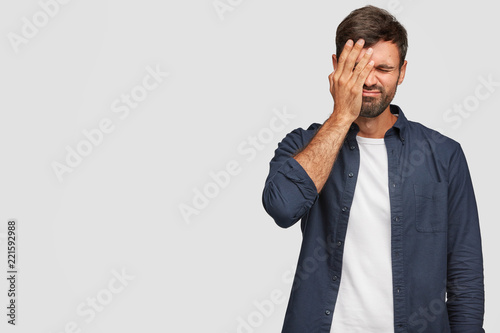 Indoor shot of handsome stressful overworked man covers face with palm, has disp Wallpaper Mural
