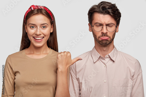 Fotografia  Hey, look at this guy! Photo of cheerful woman with broad smile points with thumb at frustrated unshaven man, express different emotions, stand against white wall