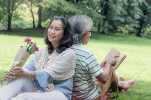 Retirement Couple, Sitting And Picnic On Green Lawn In Shady Park, With Fresh Fruits, Breads, Beverages And Books, It Mages For A Happier Holiday.