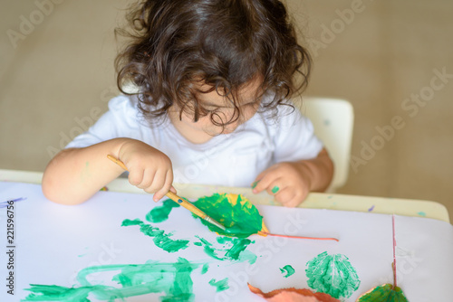 Summer or Autumn Cute little girl drawing with green paint