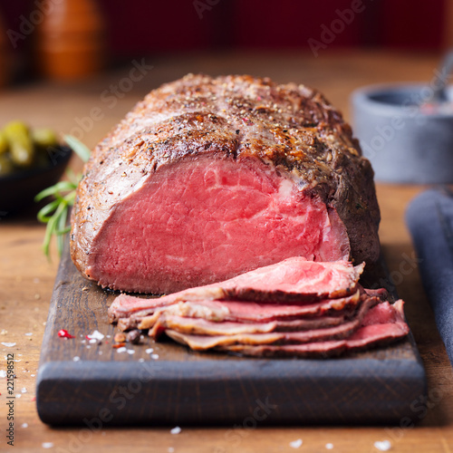Obraz na płótnie Roast beef on cutting board. Wooden background.