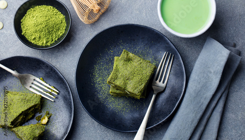 Matcha green tea cake, bars, brownie with white chocolate on a plate. Grey background. Top view.