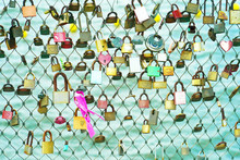 Padlocks Of Love Hangs On The Bridge Which Is Symbol Of Eternal Love Bind Together. Summer Vacation Season. Metal Grid Fence With Love Locks On The Sea Background.