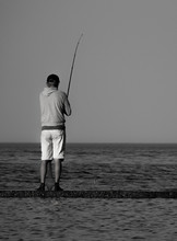 Vertical Black And White Photo Of A Lone Fisherman Standing On A Concrete Pier In The Sea.