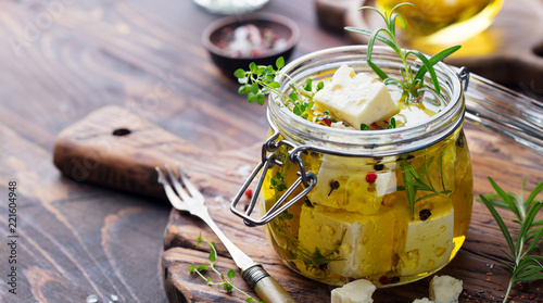 Feta cheese marinated in olive oil with fresh herbs in glass jar. Wooden background. Copy space.