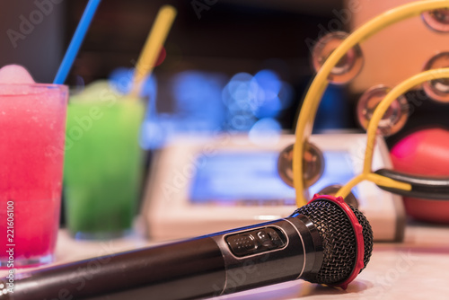 Obraz na płótnie Black microphone in karaoke club, with remote controller, melon and strawberry soda drinks, yellow tambourine and screen for singing music on stage party