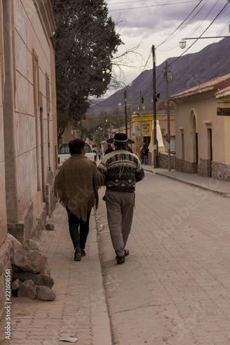 Pareja adulta con ropas tipicas caminando en una calle en Humahuaca, Jujuy, Argentina Canvas Print